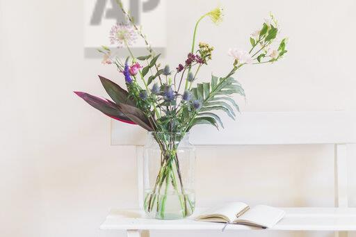 Flower vase and open calendar on white bench