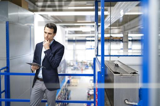 Thoughtful businessman with tablet in a factory