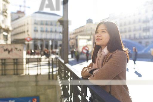 Spain, Madrid, smiling young woman at Puerta del Sol looking around
