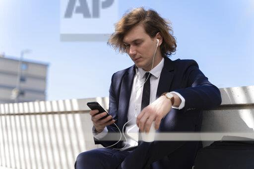 Italy, Florence, young businessman with earphones and smartphone outdoor