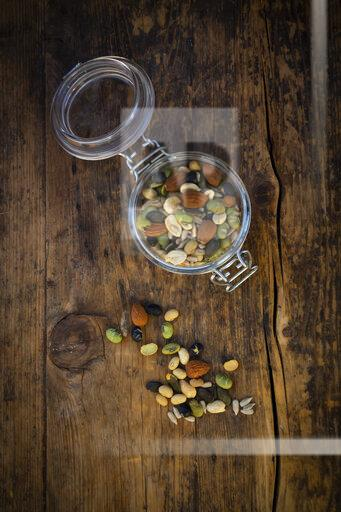 Preserving jar of roasted soy beans, seeds and nuts on wood