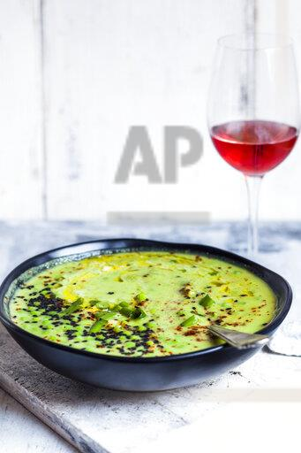 Bowl of Fresh green pea soup with spring onions and a glass of blush Wine