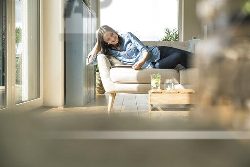 Happy woman lying on the couch at home using tablet