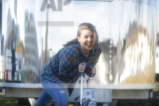 Portrait of happy young woman at a food truck with apron