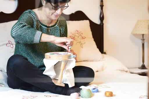 Woman embroidering sitting on bed at home