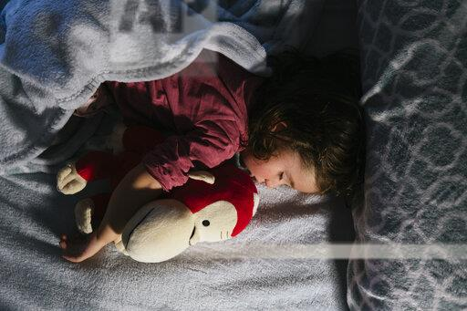 Toddler girl sleeping in bed with a soft toy dog orang-utan