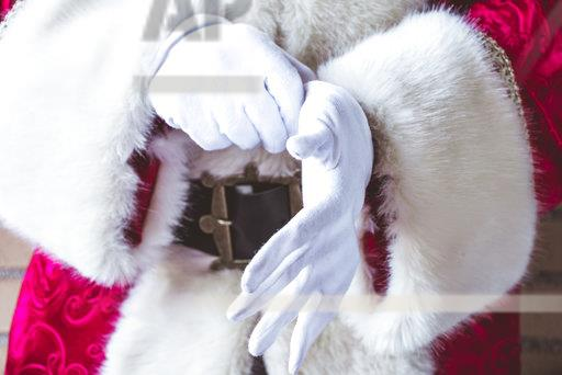 Santa Claus putting on his white gloves, close-up