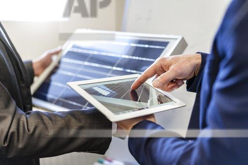 Close-up of two businessmen in office with solar cell and tablet
