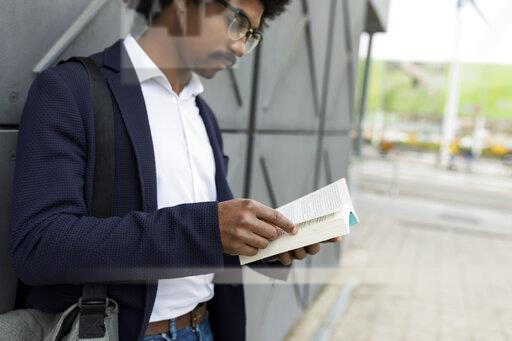 Businessman standing at a wall in the city reading book