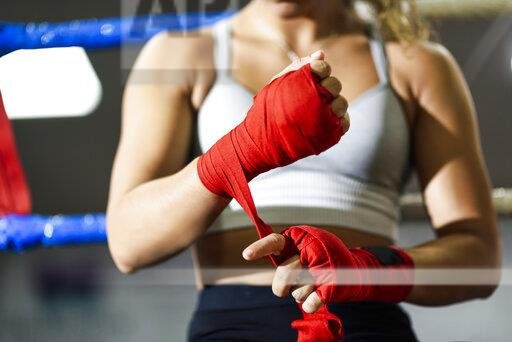Close-up of young woman tying bandage around her hand in boxing club