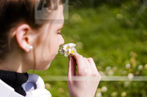 Young woman with daisies in a park
