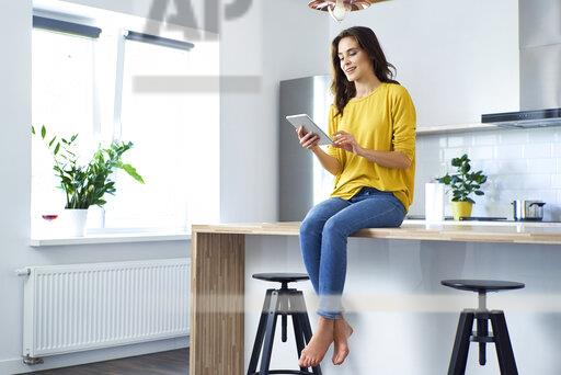 Woman sitting on kitchen counter at home, using digital tablet