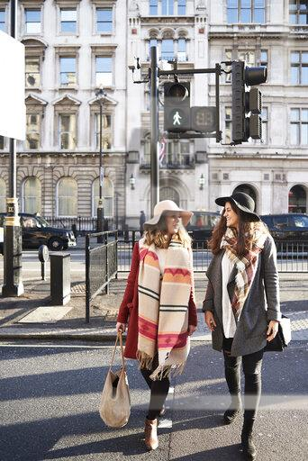 UK, London, two women in the city crossing a street