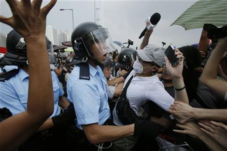 Riot police try to hold back scuffling pro-democracy protesters as an ambulance tries to leave the compound of the chief executive office in Hong Kong, Friday, Oct. 3, 2014. Hong Kong protesters on Friday welcomed an overnight offer by the territory's leader of talks to defuse the crisis over demonstrations seeking democratic reforms, though they continued to demand he resign and maintained barricades around government headquarters, frustrating staff going to work.