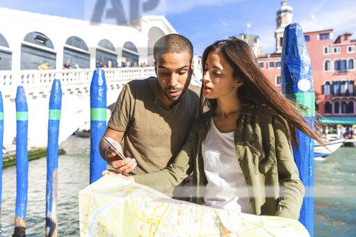Italy, Venice, couple looking at map with Rialto bridge in background