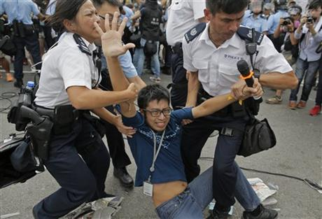 A pro-democracy protester is taken away by police officers as an ambulance tries to leave the compound of the chief executive office in Hong Kong, Friday, Oct. 3, 2014. Hong Kong protesters on Friday welcomed an overnight offer by the territory's leader of talks to defuse the crisis over demonstrations seeking democratic reforms, though they continued to demand he resign and maintained barricades around government headquarters, frustrating staff going to work.