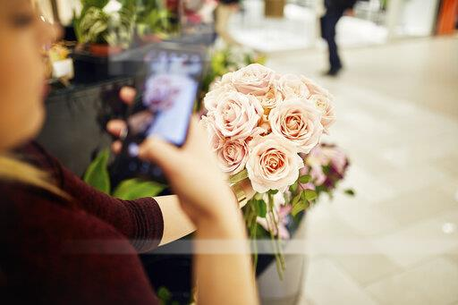 Close-up of woman holding bunch of roses in flower shop taking a cell phone picture