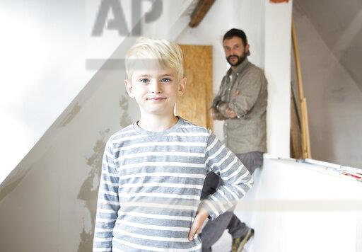 Portrait of confident boy working with father on loft conversion