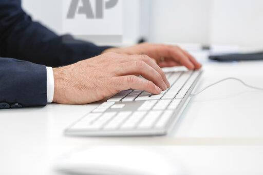 Close-up of businessman using computer keyboard at desk in office