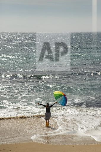 Woman with colorful umbrella standing on the beach, raised arms