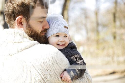 Affectionate father carrying daughter in park