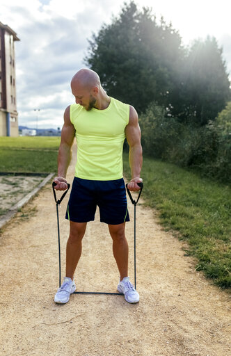 Muscular man exercising with expander outdoors