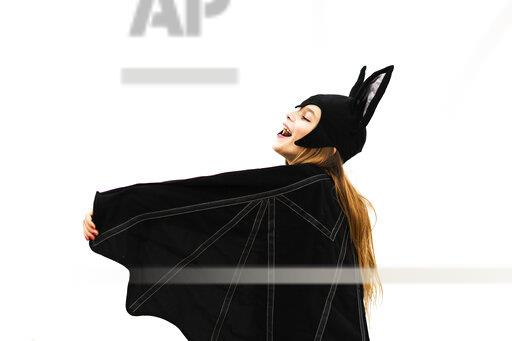 Happy girl in bat costume spreading wings