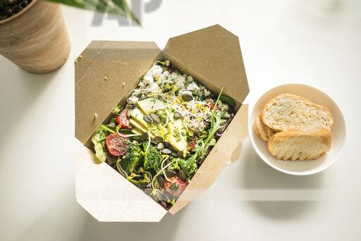 Lunch box with fresh salad on desk