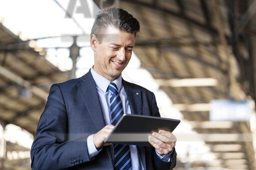 Smiling businessman using tablet at train station