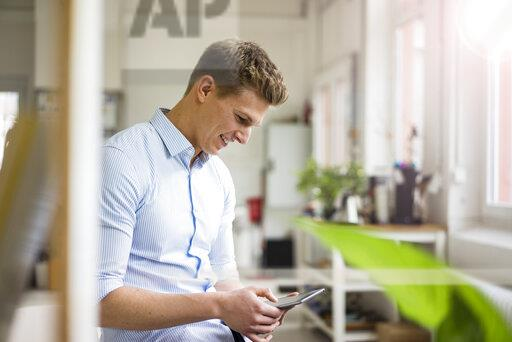 Smiling young businessman using tablet in office