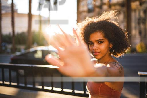 USA, Nevada, Las Vegas, portrait of young woman in the city in backlight raising her hand