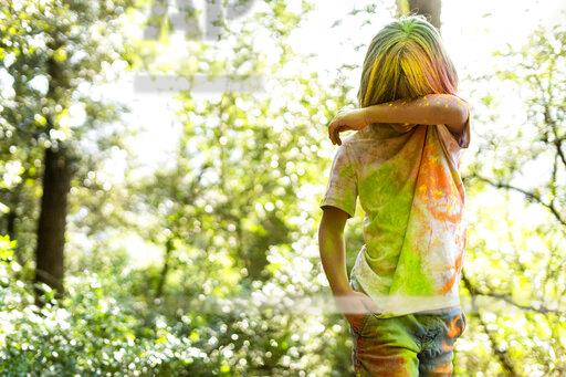 Boy full of colorful powder paint, celebrating Holi, Festival of Colors