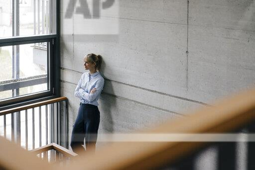 Successful businesswoman leaning on wall, looking out of window, with arms crossed