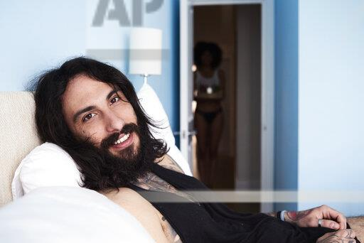Portrait of smiling tattooed man lying n bed with girlfriend in background