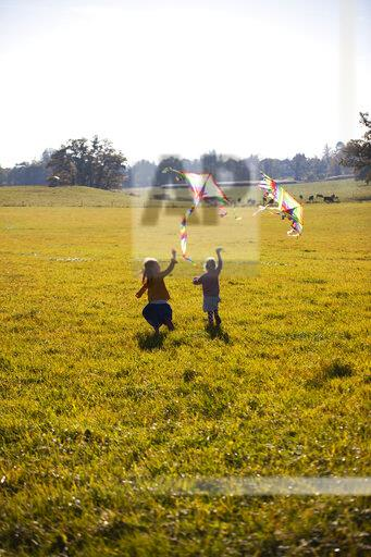 Two girls running in field with kite