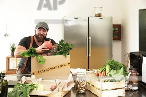 Mature man with delivery service packing organic vegetables in cardboard