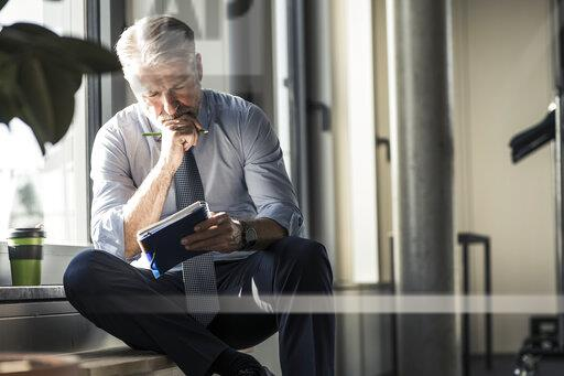 Mature businessman sitting at the window with notebook