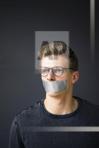 Portrait of young man with taped mouth