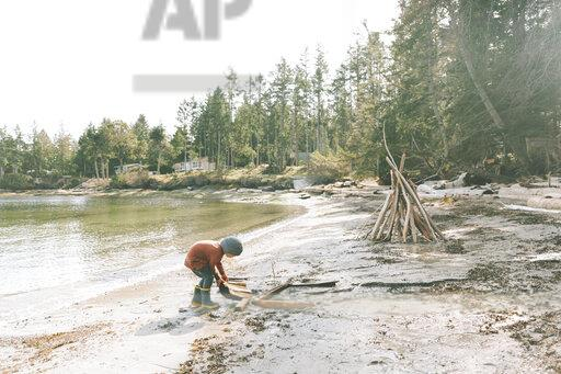 Boy playing on a the beach, building a drift wood fort