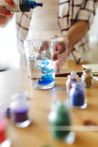 Painter filling liquid colour into glass of water, partial view