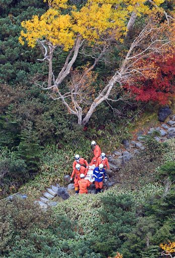 Rescuers carry a person found on Mount Ontake in central Japan Wednesday, Oct. 1, 2014. Search efforts for people missing since Saturday's surprise eruption resumed Wednesday morning. (AP Photo/Kyodo News) JAPAN OUT, MANDATORY CREDIT