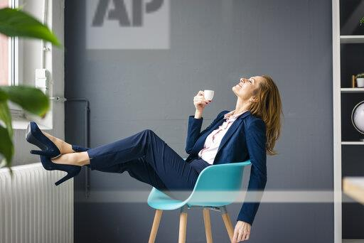 Businesswoman taking a break, sitting on a chair next to the window, drinking coffee