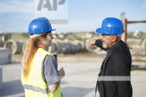 Businessman talking with female worker on industrial site