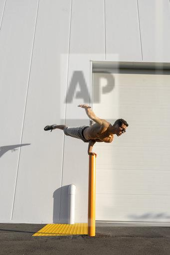 Acrobat training on a pole