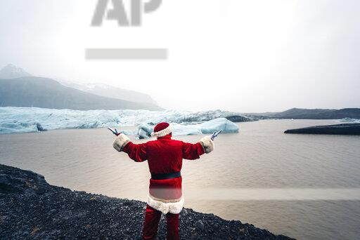 Iceland, back view of Santa Claus standing in front of glacier