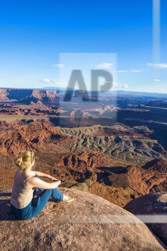 USA, Utah, Woman at a overlook over the canyonlands and the Colorado river from the Dead Horse State Park