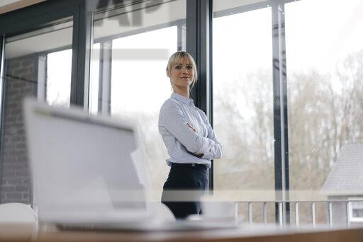 Successful businesswoman in conference room, smiling, with arms crossed