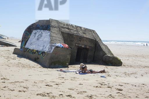 France, Gironde, woman lying on the beach in front of World War II bunker reading a book
