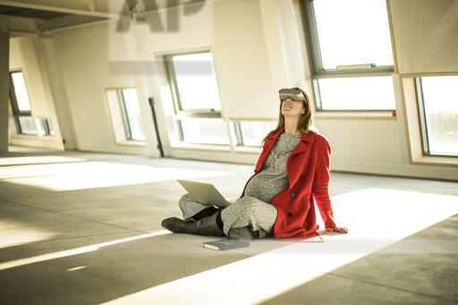 Pregnant busnesswoman sitting on floor of new office rooms, using VR goggles and laptop