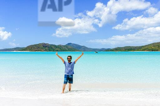 Australia, Queensland, Whitsunday Island, man with raised arms standing at Whitehaven Beach